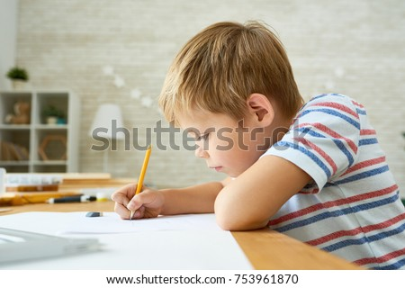 Side view portrait of diligent little boy writing or drawing carefully sitting at desk and doing homework, copy space