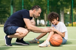 Side view portrait of focused adult man coach helping boy with knee trauma after playing basketball on the court, sad player feeling pain, touching leg. Activity And Sports Injury Concept.