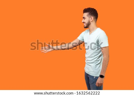 Side view portrait of friendly positive man with beard in white t-shirt giving hand to handshake and greeting, empty copy space on left for text. indoor studio shot isolated on orange background