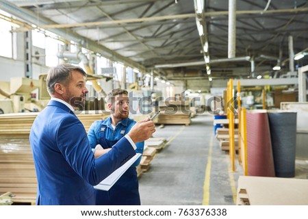 Side view portrait of handsome mature businessman touring modern factory inspecting quality of production, assisted with young workman, copy space #763376338