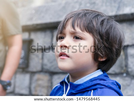 Side view portrait of little boy standing next to brick wall and looking out with curious face, Kid playing outside. Child with dramatic face #1479568445