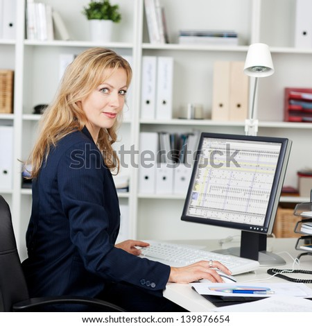 Side view portrait of mid adult businesswoman using computer at office desk