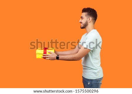 Side view portrait of positive generous brunette man with beard in white t-shirt smiling and giving gift box, sharing holiday present, charity concept. indoor studio shot isolated on orange background