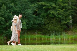 Side view portrait of romantic adult couple embracing while walking by river in rustic countryside scenery, copy space