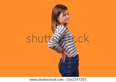 Side view portrait of sick woman with brown hair in long sleeve striped shirt standing with grimace of pain, holding back, suffering strong backache. indoor studio shot isolated on orange background