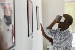 Side view portrait of smiling African-American man wearing VR gear while enjoying immersive experience at modern art gallery exhibition, copy space