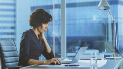 Side View Portrait of the Beautiful Businesswoman Working on a Laptop in Her Modern Office with Cityscape Window View. Female Executive Uses Computer.