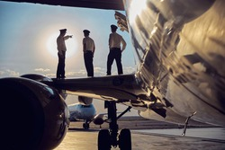 Side view portrait of three unrecognizable persons looking to the sunny sky while standing on the wing of big passenger airplane