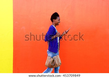 Side view portrait of trendy young black woman walking and  reading text message on her mobile phone