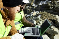 Side view  portrait of two industrial  workers wearing reflective jackets, one of them African, using laptop on mining worksite outdoors