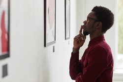 Side view portrait of young African-American man looking at paintings and thinking at art gallery or museum exhibition, copy space