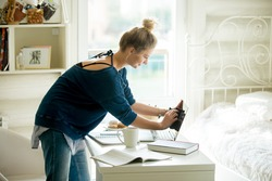 Side view portrait of young beautiful happy smiling casual woman wiping laptop screen, doing housework in her room. Indoors image