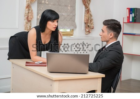 Side view portrait of young business couple flirting near the table at workplace in office, man sitting at the desk and looking at sexy standing colleague, relationship at work concept