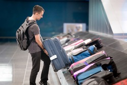Side view portrait of young handsome man passenger in 20s with carry-on backpack collecting his luggage at conveyor belt in arrivals lounge of airport terminal building