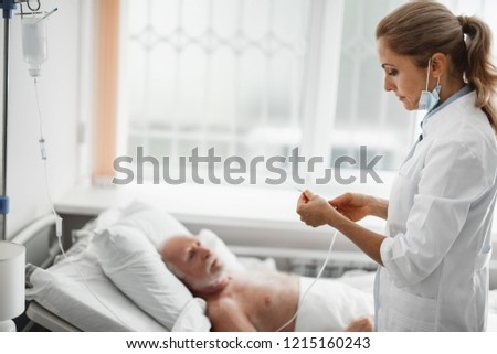 Side view portrait of young lady in white lab coat holding needle for intravenous infusion. Old man lying in bed on blurred background #1215160243