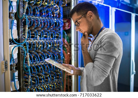 Side view portrait of young network engineer looking at digital tablet thoughtfully while working with servers in data center