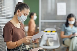 Side view portrait of young woman wearing mask and holding document while waiting in line in office, copy space