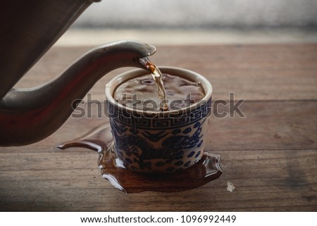 Side view. Pour water from the antique steel teapot into the teacup overflow on wood table vintage. ストックフォト ©