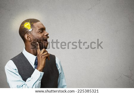 Side view profile headshot happy man thinking found solution for problem isolated grey wall background with copy space light bulb. Human face expression emotion feeling body language perception iq