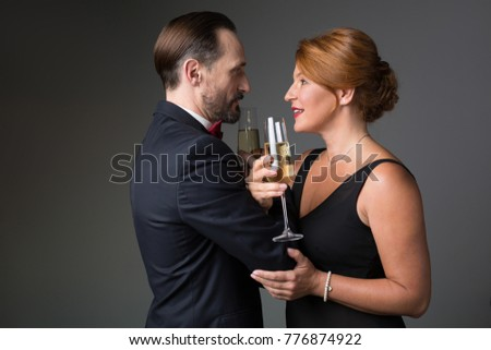 Side view profile of affectionate middle-aged married couple are drinking champagne while touching their arms to each other. They are looking into eyes with love and smiling. Isolated #776874922
