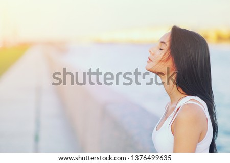 Side view profile portrait of a happy brunette woman relaxing breathing fresh air outdoors in summer Girl closed eyes doing deep breath exercises. Positive emotion success, peace of mind, zen concept.