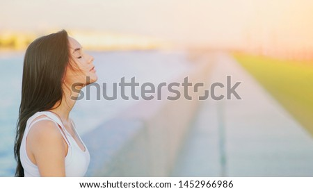 Side view profile portrait of a happy brunette woman relaxing breathing fresh air outdoors in summer Girl close eyes doing deep breath exercises. Positive emotion success, peace of mind, zen concept