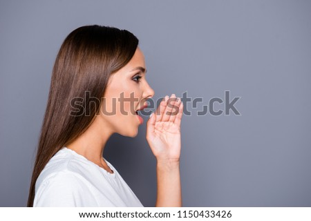 Side-view profile portrait of attractive woman telling news, shouting and holding hand near her open mouth isolated on gray background with copyspace