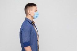 Side view, protection against contagious disease, coronavirus. Man wearing hygienic mask to prevent infection, airborne respiratory illness, Covid-2019. indoor studio shot isolated on gray background