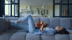Side view relaxed girl playing guitar in living room. Dreamy woman lying on couch with musical instrument. Female guitarist resting on sofa. Attractive lady playing slow music on acoustic guitar