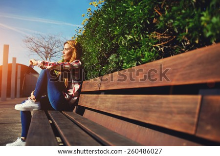 Side view seated woman on the bench enjoying nature in sunny day outdoors, charming young girl relaxing in the spring park, female student relaxing at campus, flare sun light