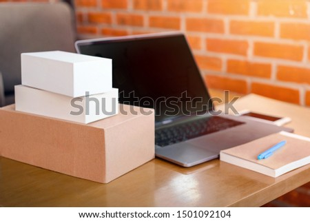 Side view, shipping, online shopping, newcomers, small business owners are small businesses, SME entrepreneurs or Asian freelance workers. That works with products boxes and smart phone and laptop