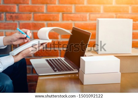 Side view, shipping, online shopping, newcomers, small business owners are writing orders, trade names on usable receipts, SME entrepreneurs or freelance workers. That works with products box, laptop