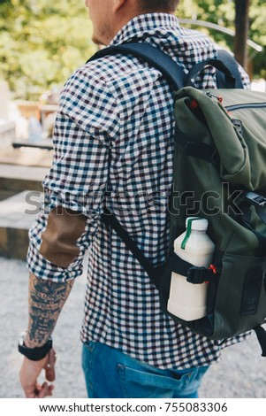 Side view shot. Man walking with plastic bottle of detox nutrition milk drink outdoor in the street. #755083306