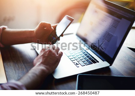 Side view shot of a man's hands using smart phone in interior, rear view of business man hands busy using cell phone at office desk, young male student typing on phone sitting at wooden table, flare #268450487