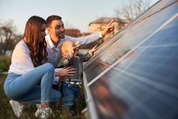 Side view shot of a young modern family with a little son getting acquainted with solar panel on a sunny day, green alternative energy concept