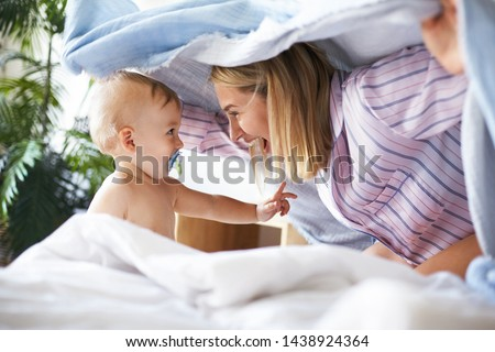 Side view shot of charming joyful young woman in pajamas playing hide and seek with toddler daughter. Adorable cute infant child sucking on pacifier looking at mother, having playful facial expression