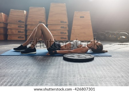 Side view shot of fitness woman resting on exercise mat with a heavy weight plate on floor. Female athlete lying on her back after a gym workout