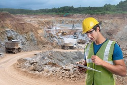Side view shot of  industrial workers wearing reflective jackets and hardhats standing on mining worksite outdoors using digital tablet, copy space