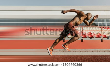 Side view shot of male sprinter running on the sport track. Athlete runner doing workout at the stadium