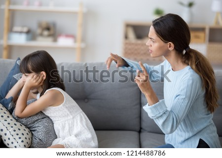 Side view single mother screams shouts at little daughter scolding her. Kid not listen ignoring mom close cover her ears with fingers. Complicated relationships with child and family conflict concept