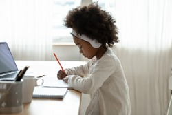 Side view small African girl wear wireless headphones doing homework seated at desk in her room. Focused schoolgirl listen audio lesson use laptop writes on workbook. E-learning, homeschooling concept