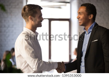 Side view smiling african caucasian businessmen executive manager greeting welcoming corporate client. Boss congratulate job candidate with successfully passing interview. Hiring or rewarding concept #1395353000