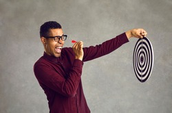 Side view smiling confident young black man aiming red dart at shooting target determined to throw it and hit bullseye. Using chance, accepting challenge, achieving business goal and objective concept