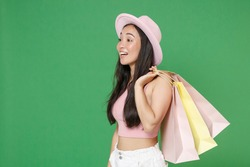 Side view smiling young asian woman girl in pink clothes hat isolated on green background. People lifestyle concept. Mock up copy space. Hold package bag with purchases after shopping, looking aside