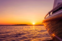 Side view Speeding fishing motor boat with drops of water. Blue ocean sea water wave reflections at the sunset. Motor boat in the blue ocean. Ocean yacht. Sunset at the sailboat deck