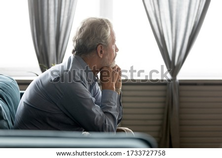 Side view thoughtful middle aged mature grandfather sitting on couch, looking away at window. Pondering old senior hoary man thinking of psychological health problems, spending time alone at home.