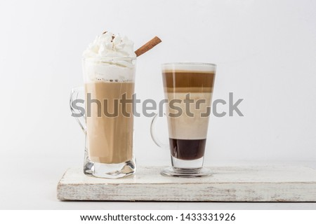 Side view Two cups of Cappuccino and Chocolate Mocha with Cinnamon stick and whipped cream on top over wooden coaster #1433331926