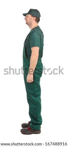 Side view. Worker in green overalls. Isolated on a white background