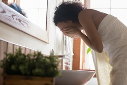 Side view young african american woman wrapped in towel after showering, bending over sink, washing off mask or peeling, cleaning her face with pure running water. Daily hygiene skincare routine.