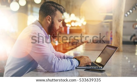 Side view.Young bearded businessman wearing blue shirt,sitting at table in cafe and uses laptop.Nearby is smartphone and cup of coffee. Man checks email on computer. Freelancer working outside office